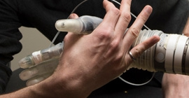 a robotic hand grasping a human hand